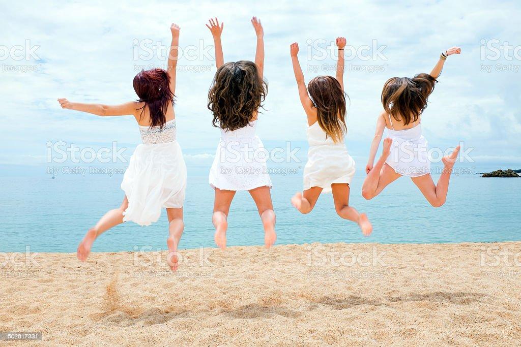 Adolescentes de sauter sur la plage photo libre de droits