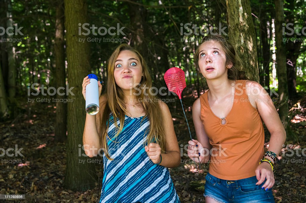 Teen girls make faces chasing insects in a forest stock photo