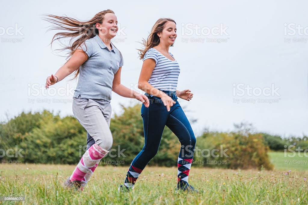 Teen girls running together on summer meadow stock photo