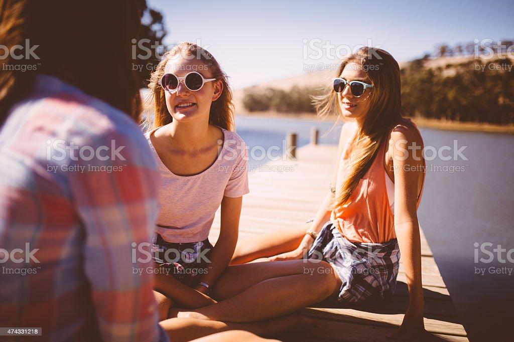 Teen girls talking on a lakeside jetty on summer vacation stock photo