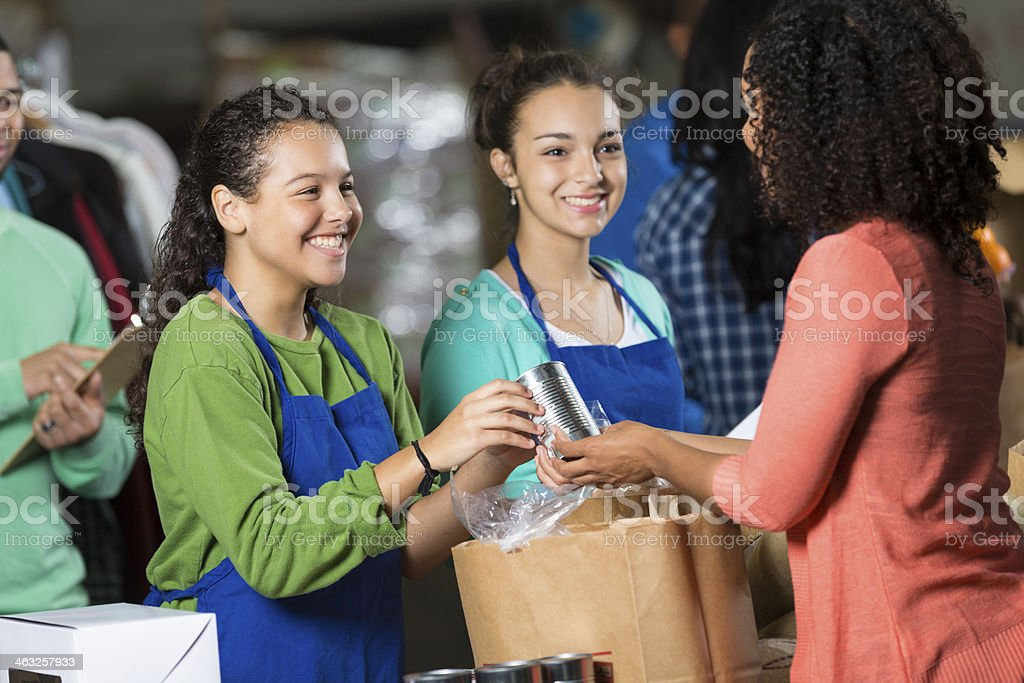 Teen girls volunteering at food bank, receiving donated groceries stock photo