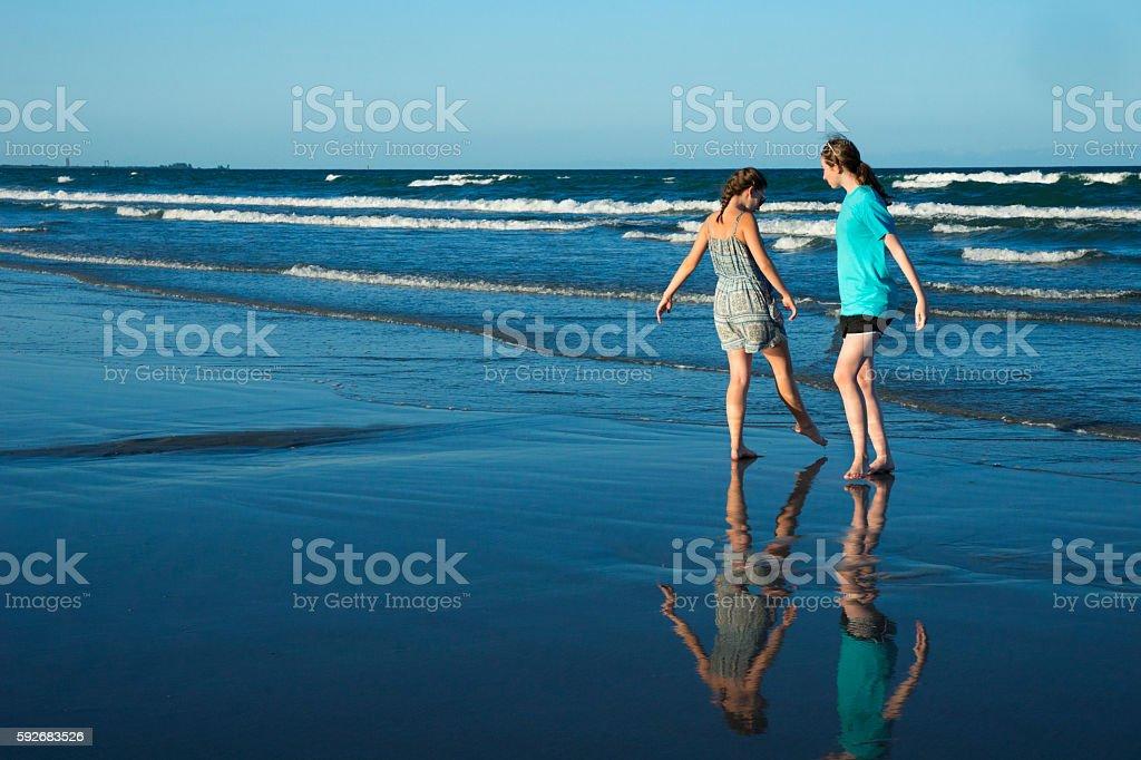 Teen girls walk on wet sandy beach at sunset stock photo