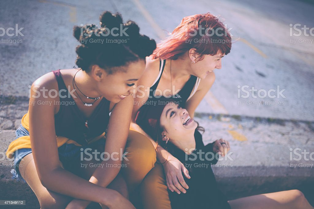 Teen girls with grunge style laughing on the pavement together stock photo