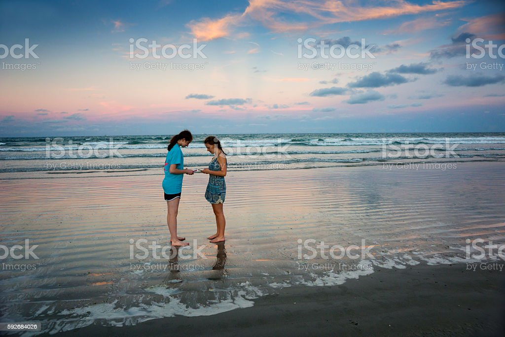 Teen girls with smartphones on ocean beach at sunset stock photo