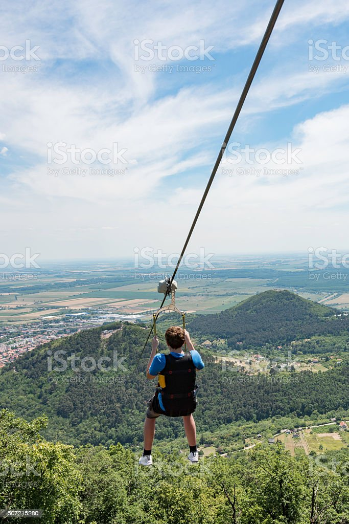 Teen going on a zipline adventure above a valley stock photo