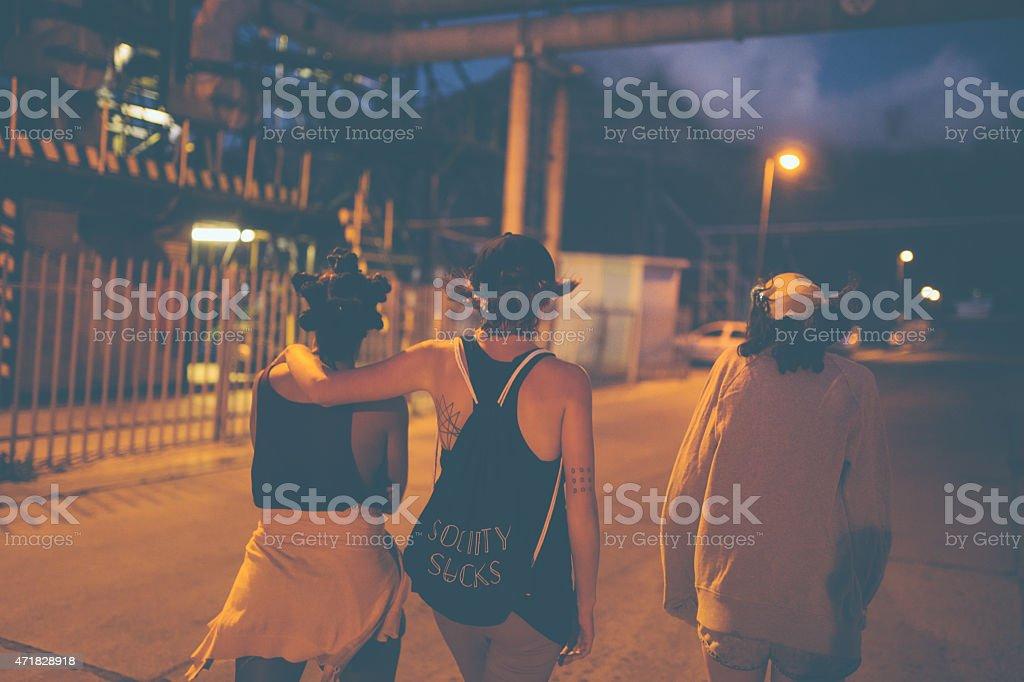 Teen grunge girl friends walking on urban road at night stock photo