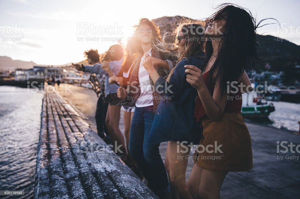 Teen hipster friends dancing on the pier at sunset stock photo