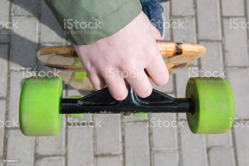 Teen hold longboard in hand. Close up. stock photo