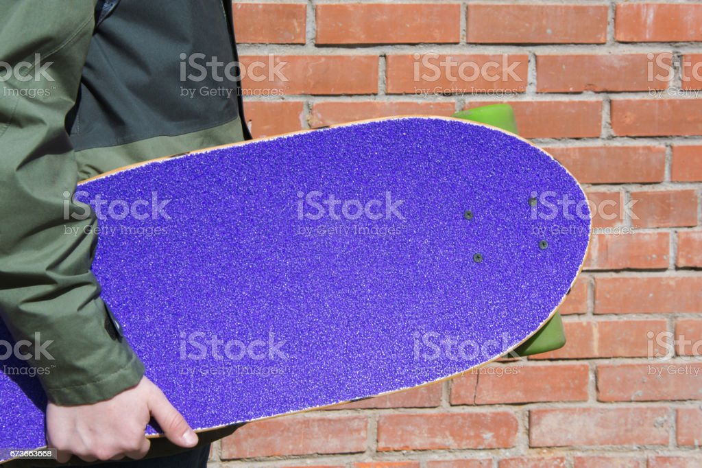 Teen hold purple longboard near the brick wall. Shallow depth of field. Close up. stock photo