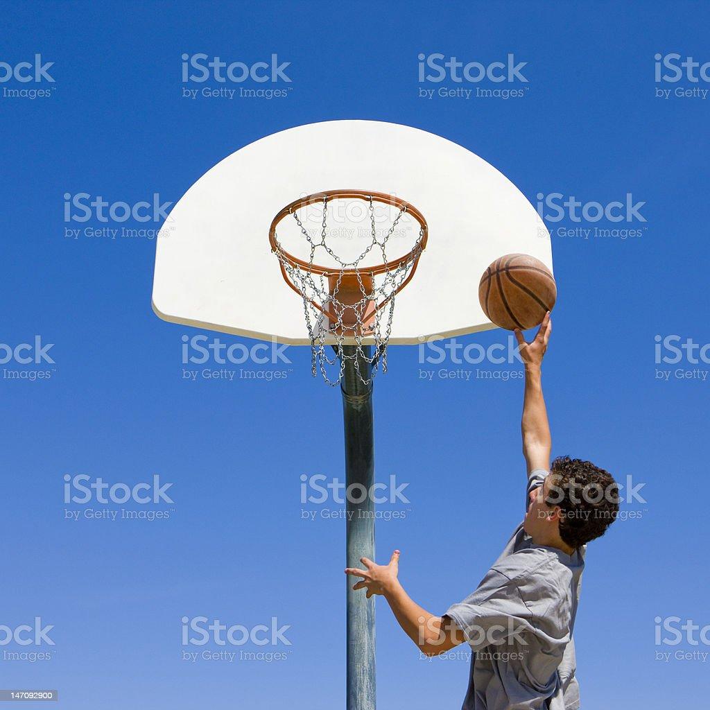 Teen jumps and shoots basketball stock photo