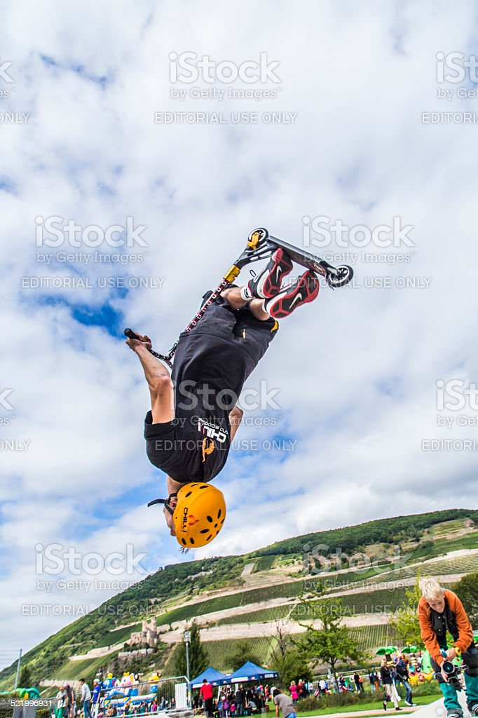 teen jumps with scooter over a ramp with salto stock photo