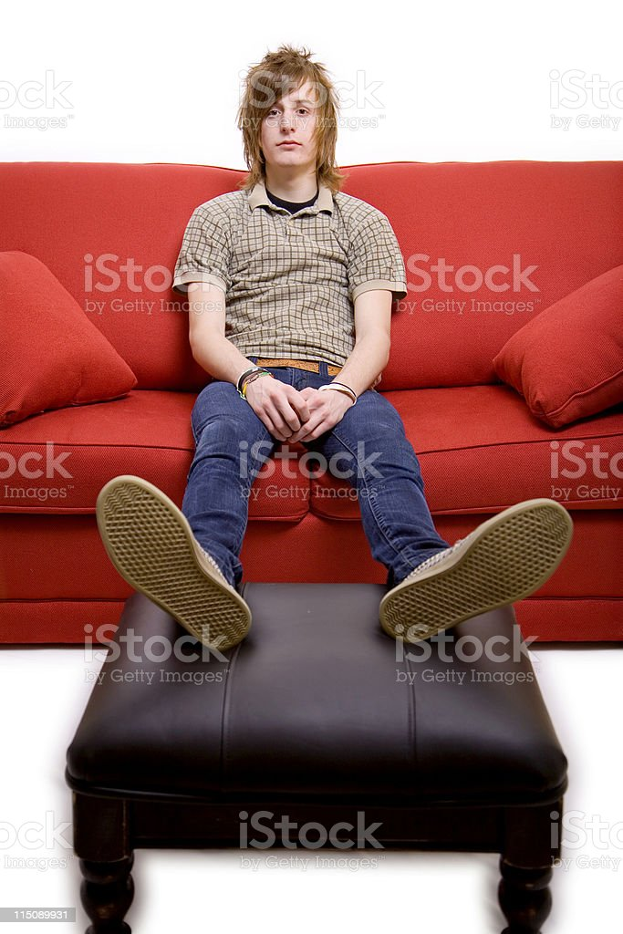 teen life scenes - male on couch stock photo