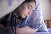Teen Lying Under Blanket during the day using smartphone