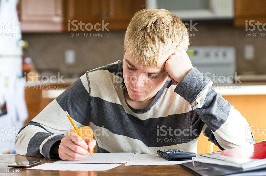 Teen Male Doing Homework at Kitchen Table royalty-free stock photo