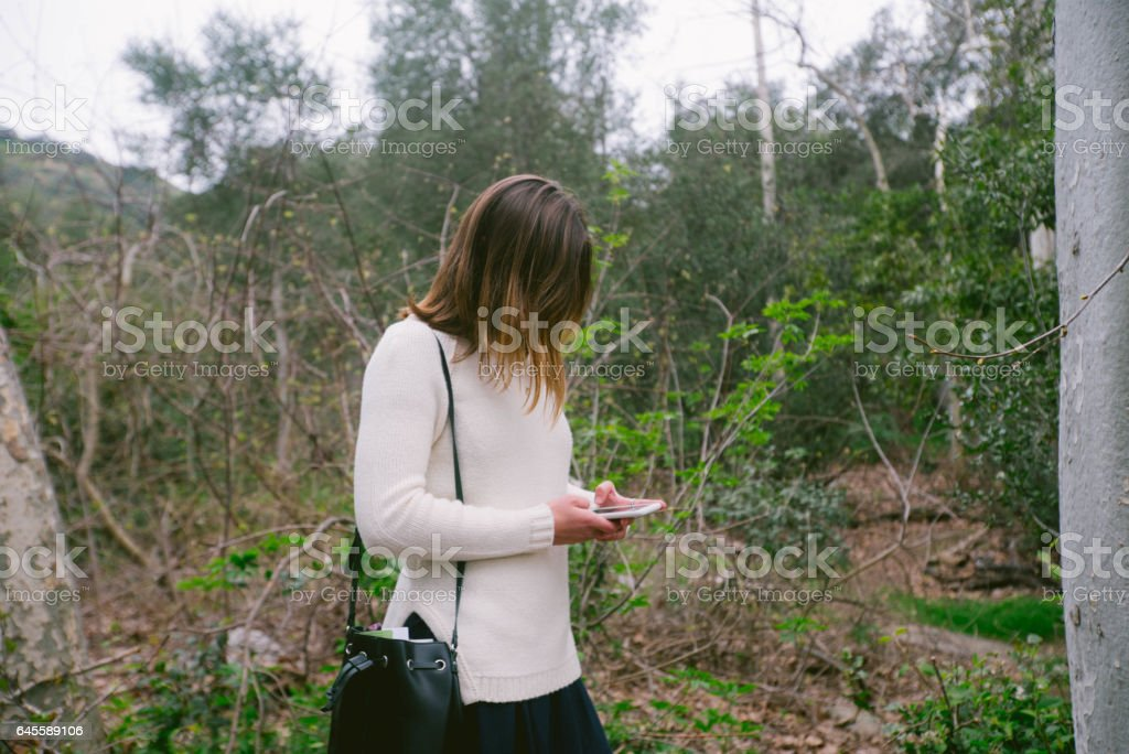 Teen On Cell Phone In Nature Near Trees stock photo
