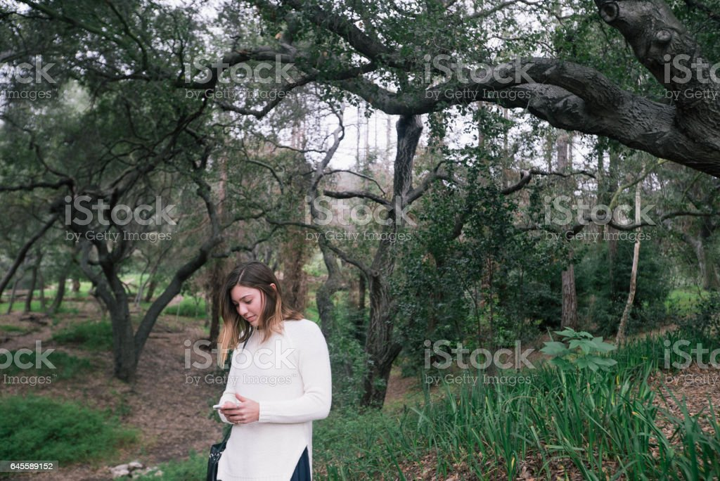 Teen On Phone In Wilderness stock photo