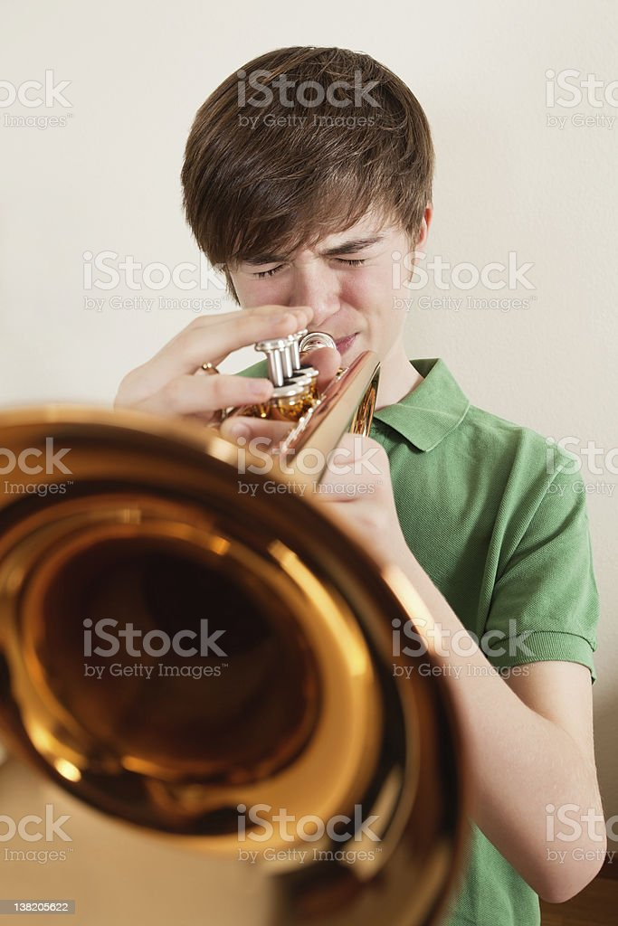 Teen playing gold trumpet royalty-free stock photo