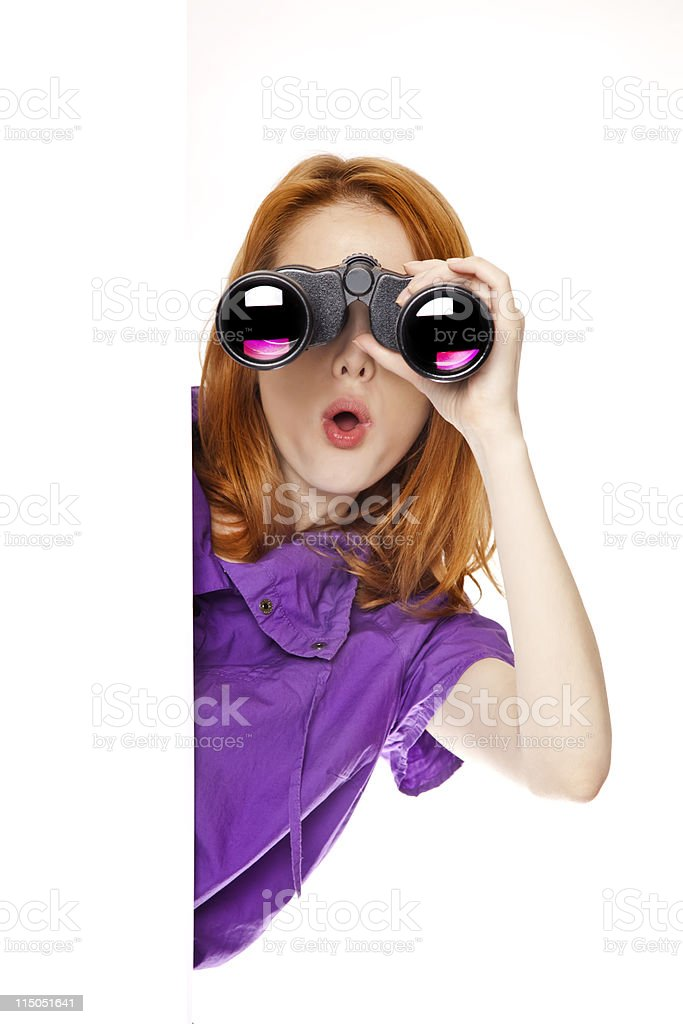 Teen redhead girl with binoculars isolated on white background stock photo