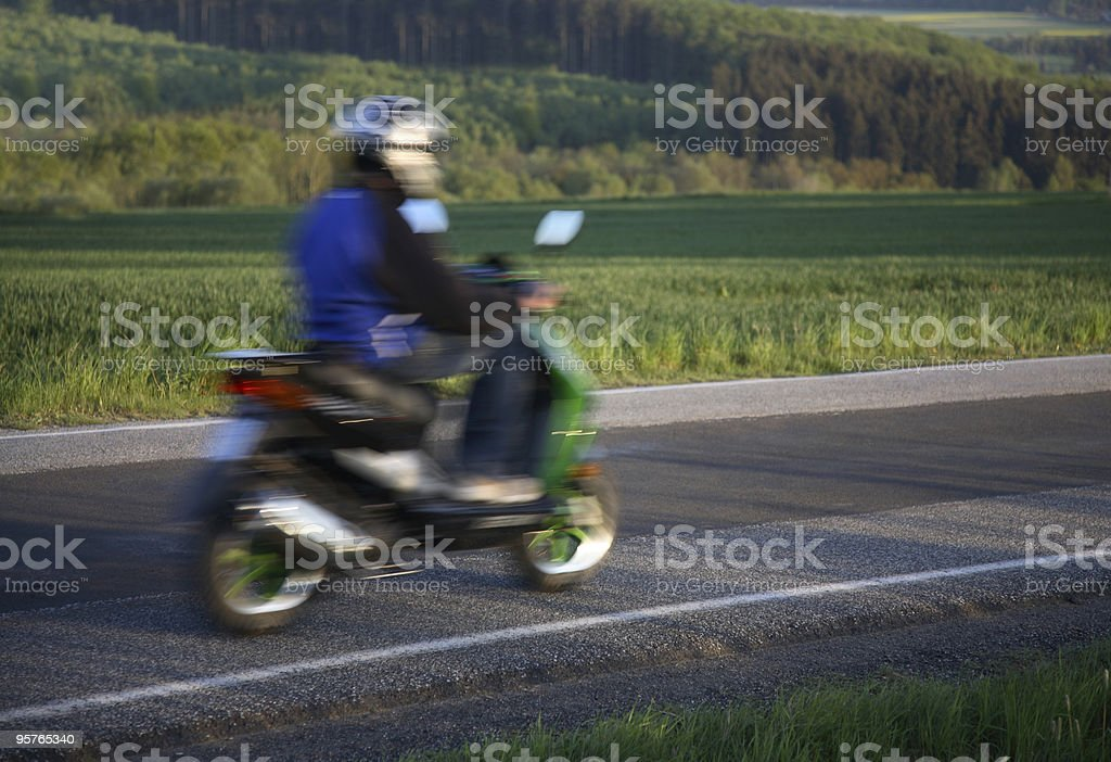 Teen riding home on his moped, motion blur royalty-free stock photo
