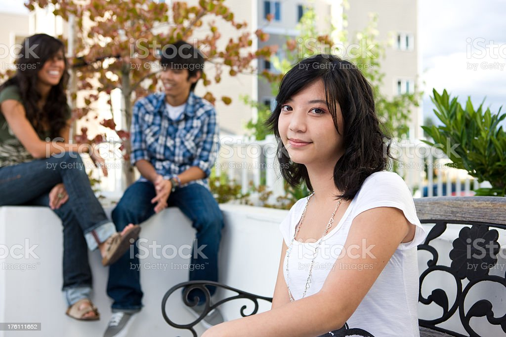 Teen Sitting On Bench With Friends Talking stock photo