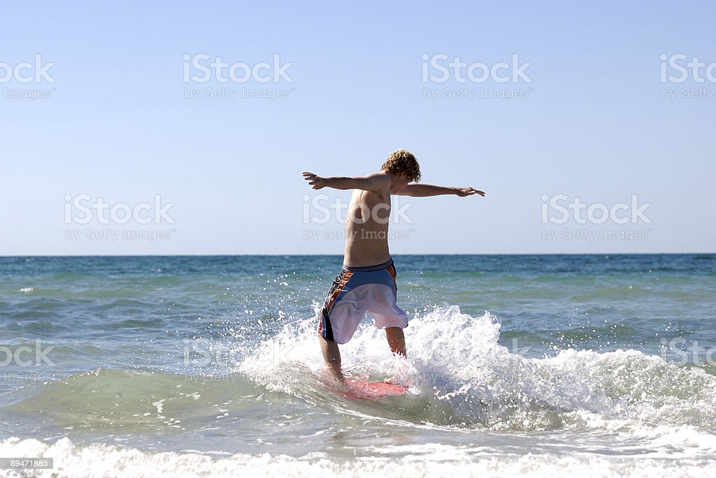 Teen skimboarding at the beach. stock photo
