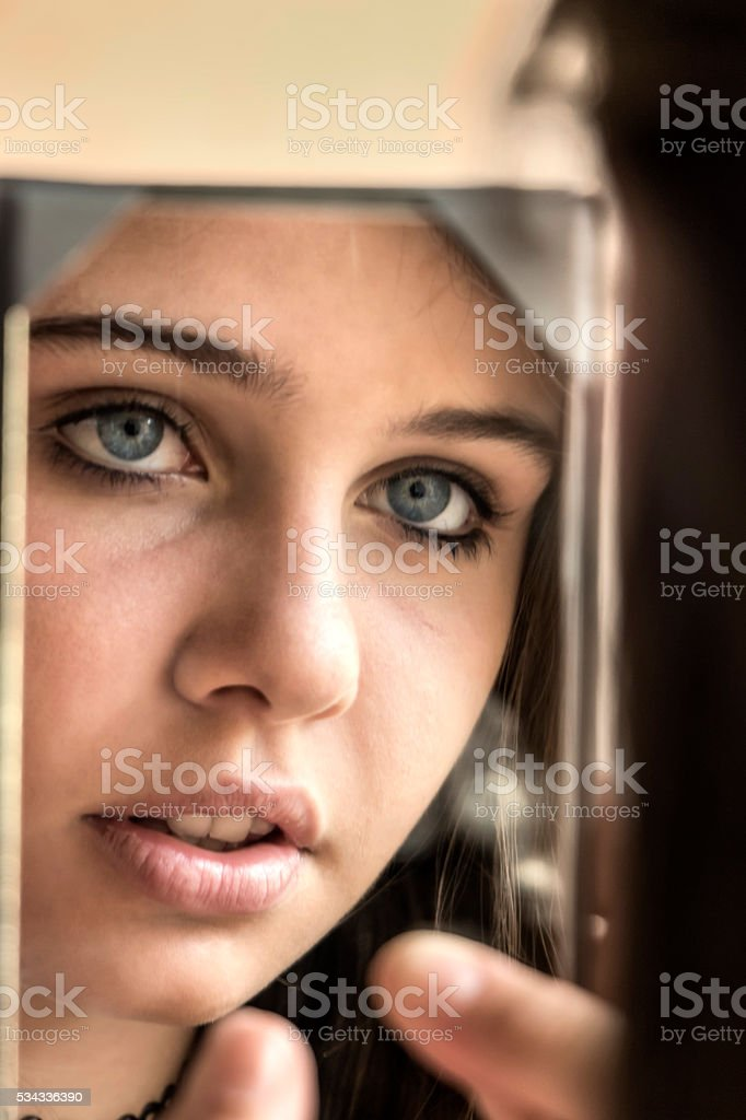 Teen smiling in front of the mirror stock photo