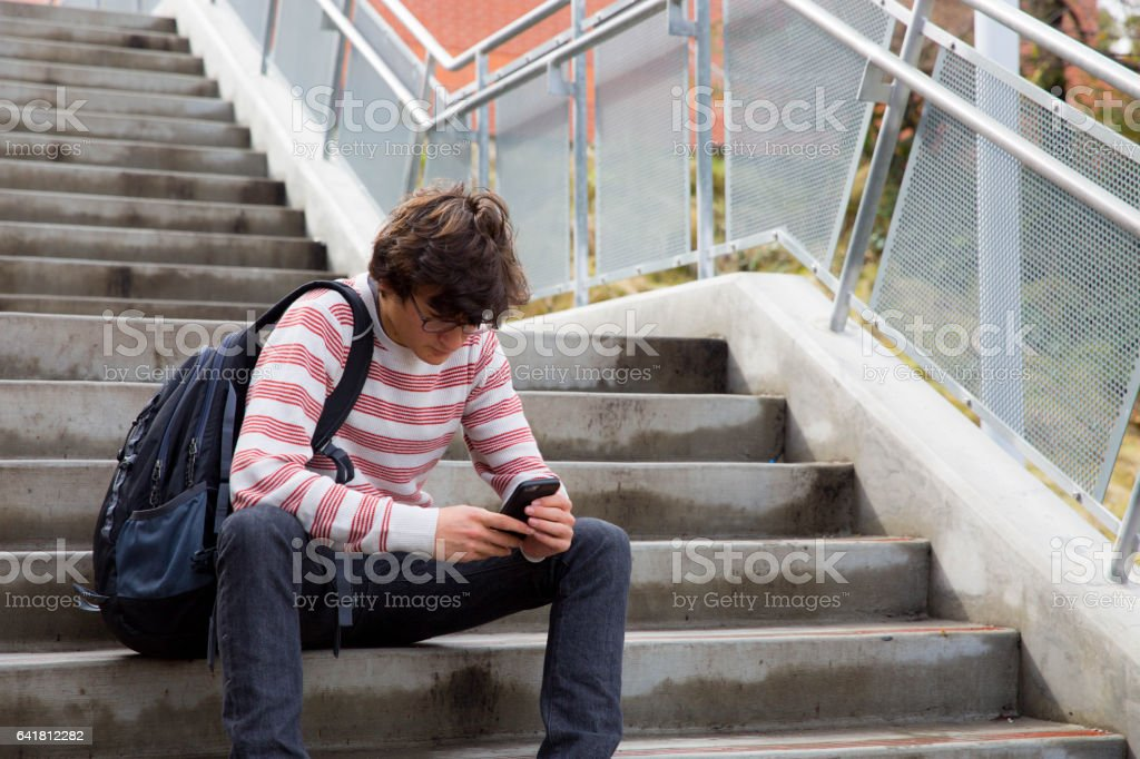 Teen Staring Into Phone On Stair Case During Day stock photo