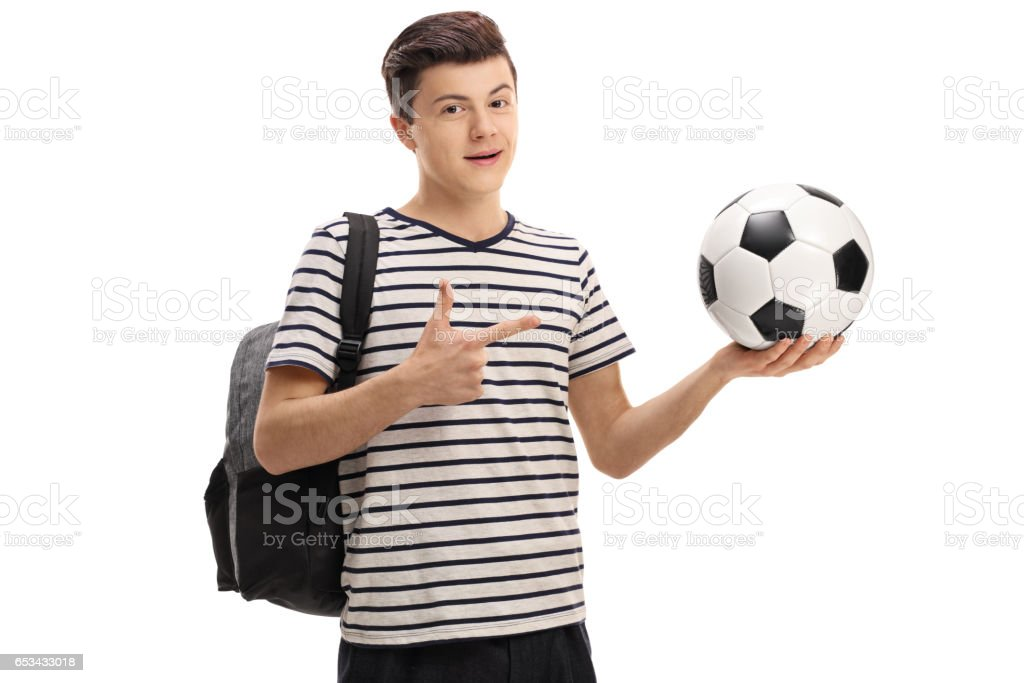 Teen student holding a football and pointing stock photo