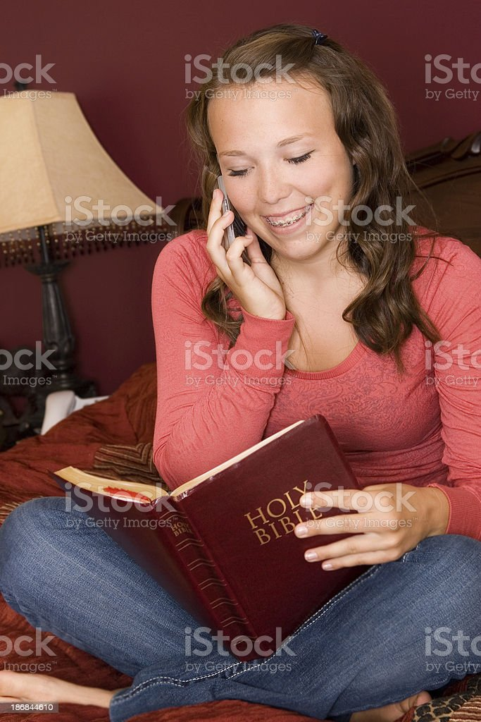 Teen talks on cell phone while looking at Bible royalty-free stock photo