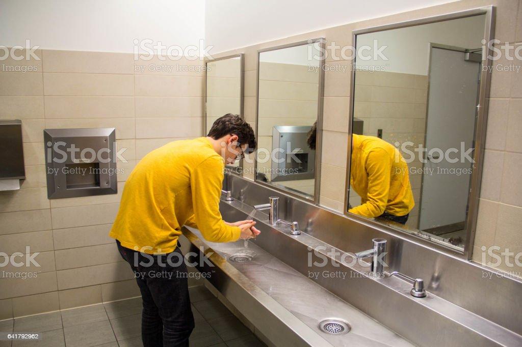 Teen Washing hands in Public Bathroom stock photo
