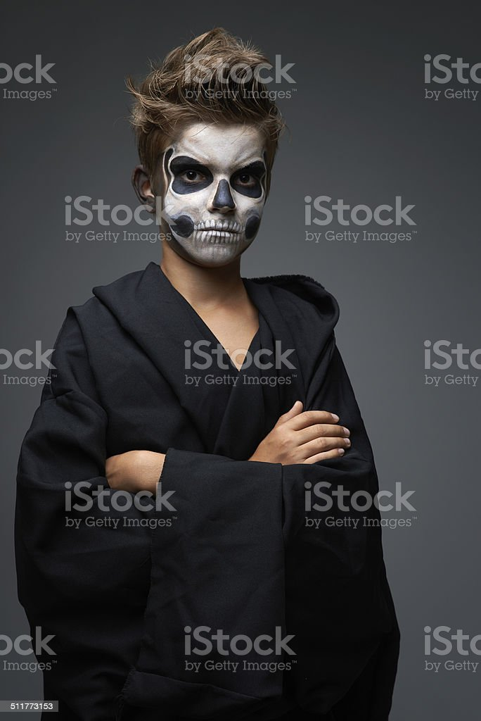 Teen with make-up of the skull in black cape stock photo