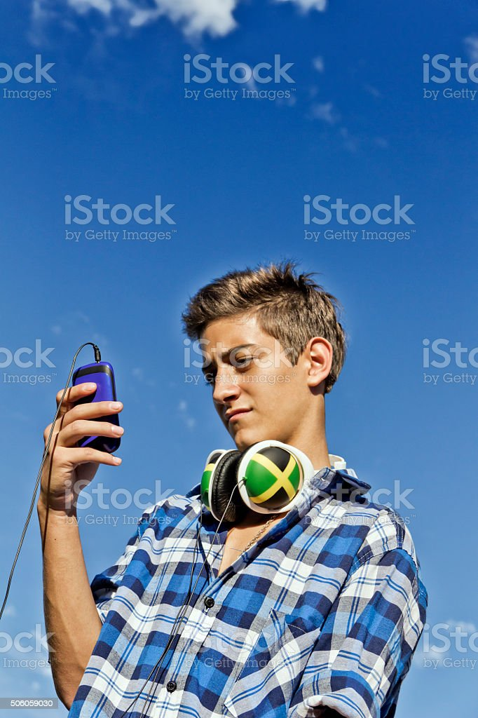 Teen with smartphone and headphones stock photo