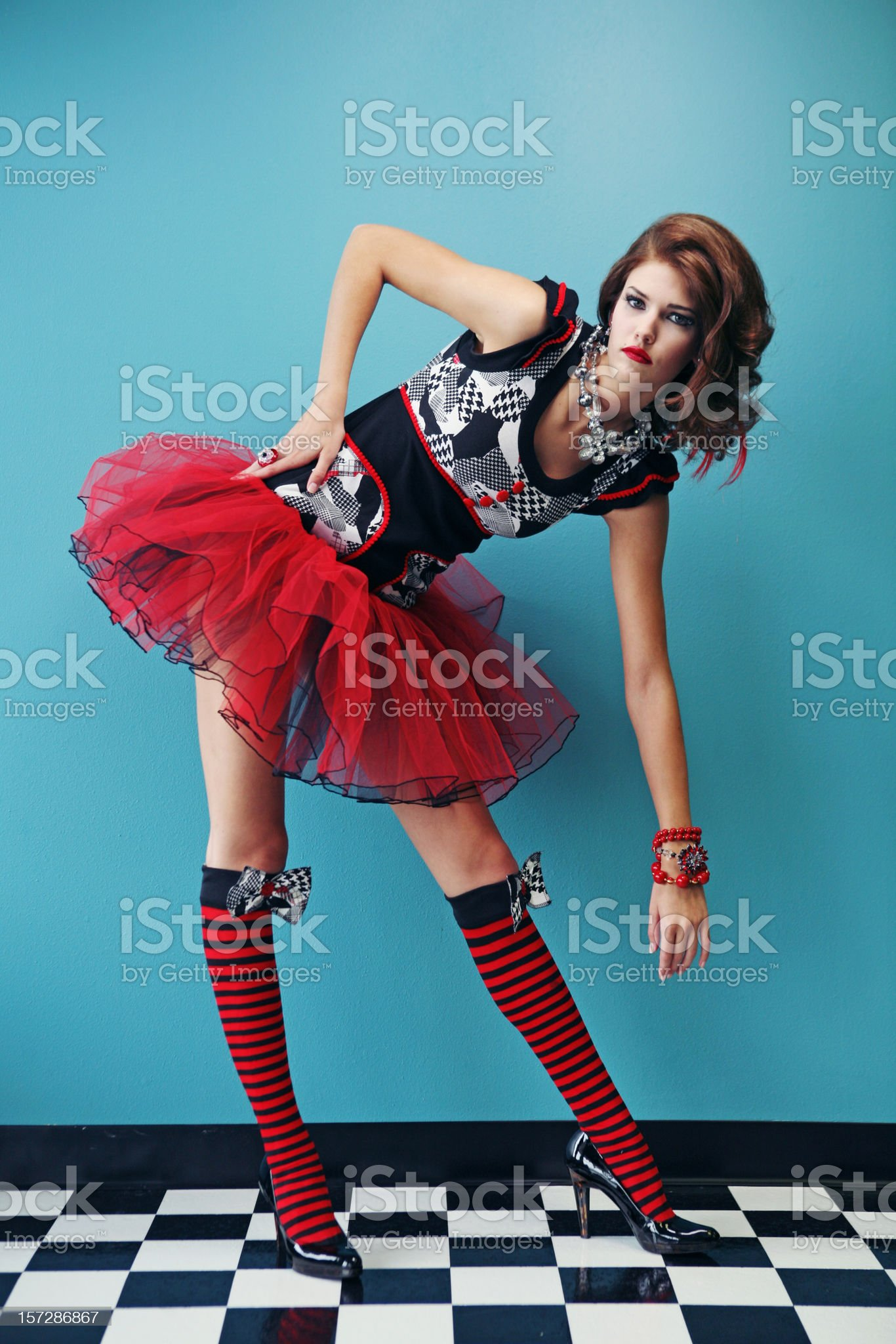 Teen Woman in Red and Black Dress on Tile Floor royalty-free stock photo
