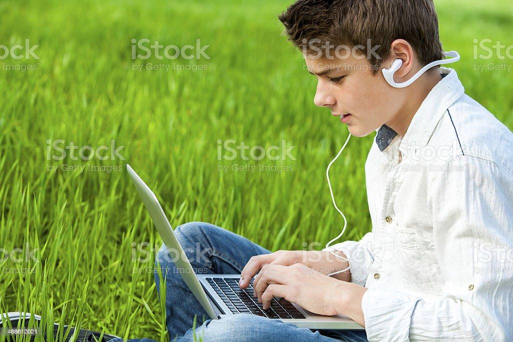 Adolescents travaillant sur ordinateur portable dans green field. photo libre de droits