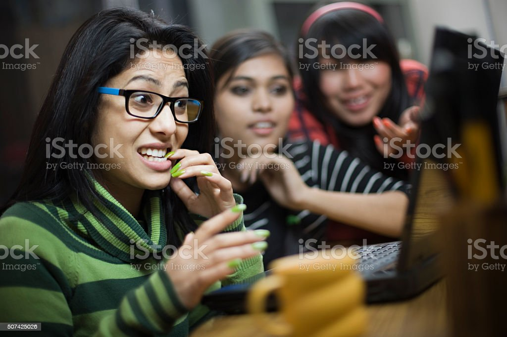 Teenage Asian girl biting fingernail and using laptop with friends. stock photo