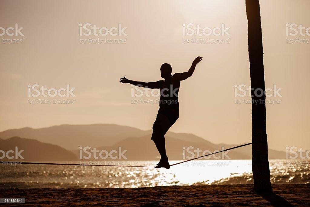 teenage balancing on slackline with sea view stock photo