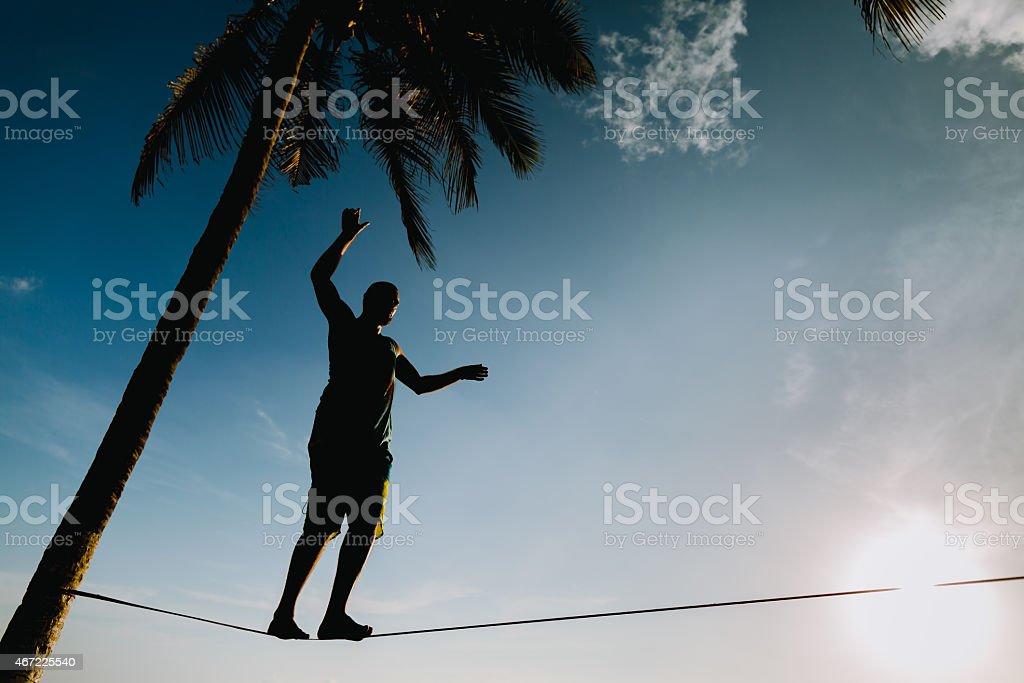 teenage balancing on slackline with sky view stock photo