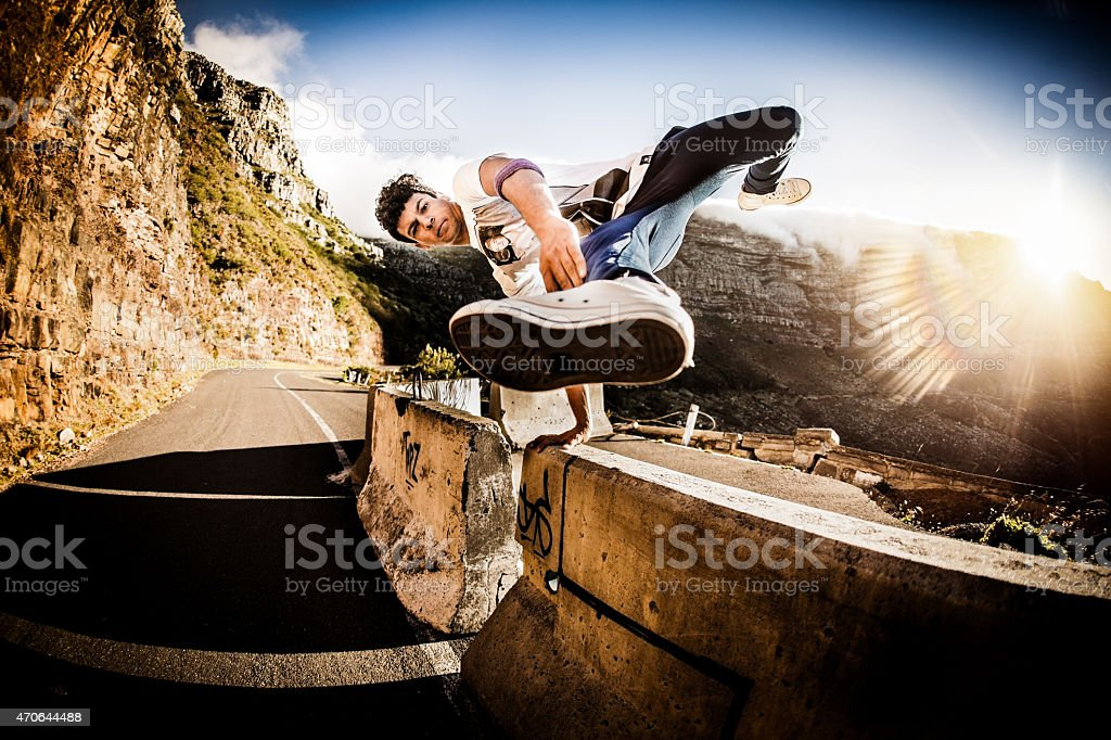 Teenage b-boy keeping fit practicing moves on a wall outdors stock photo