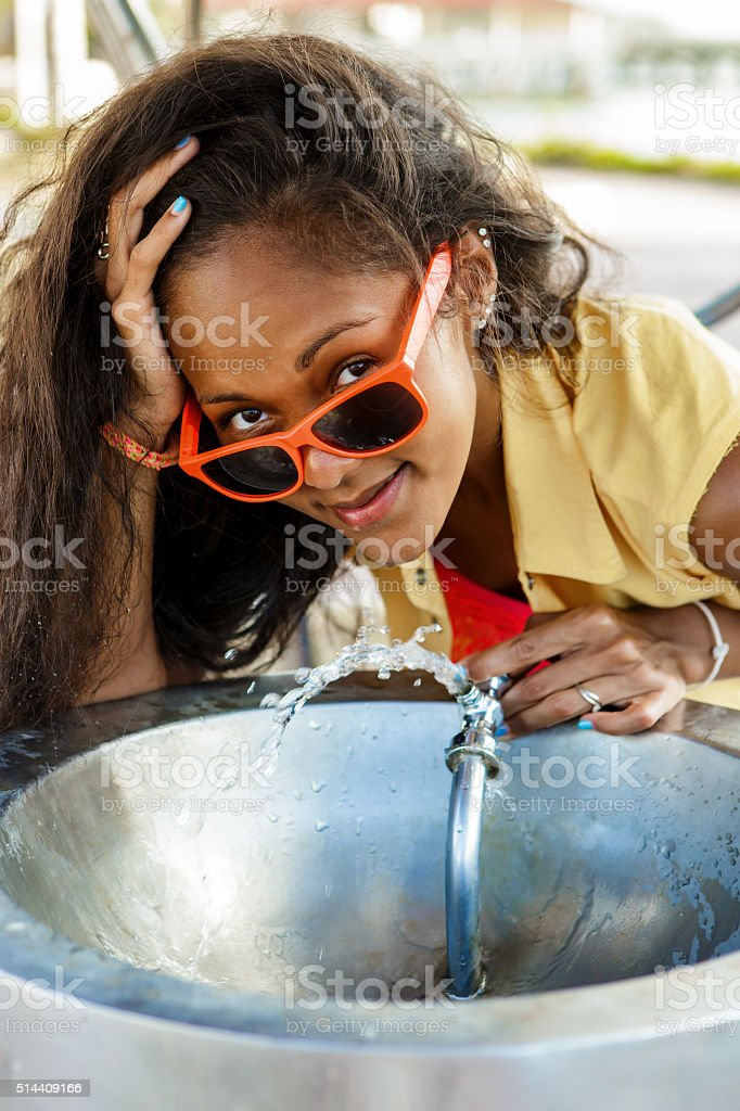 Teenage black girl in sunglasses drinking from water drinking fountain. stock photo