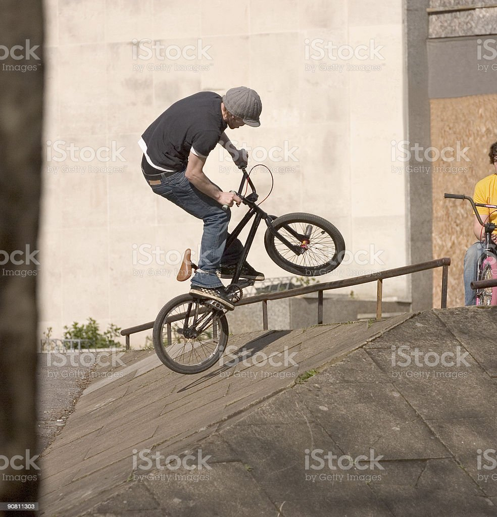 Teenage BMX biker performing a stunt in an urban street royalty-free stock photo