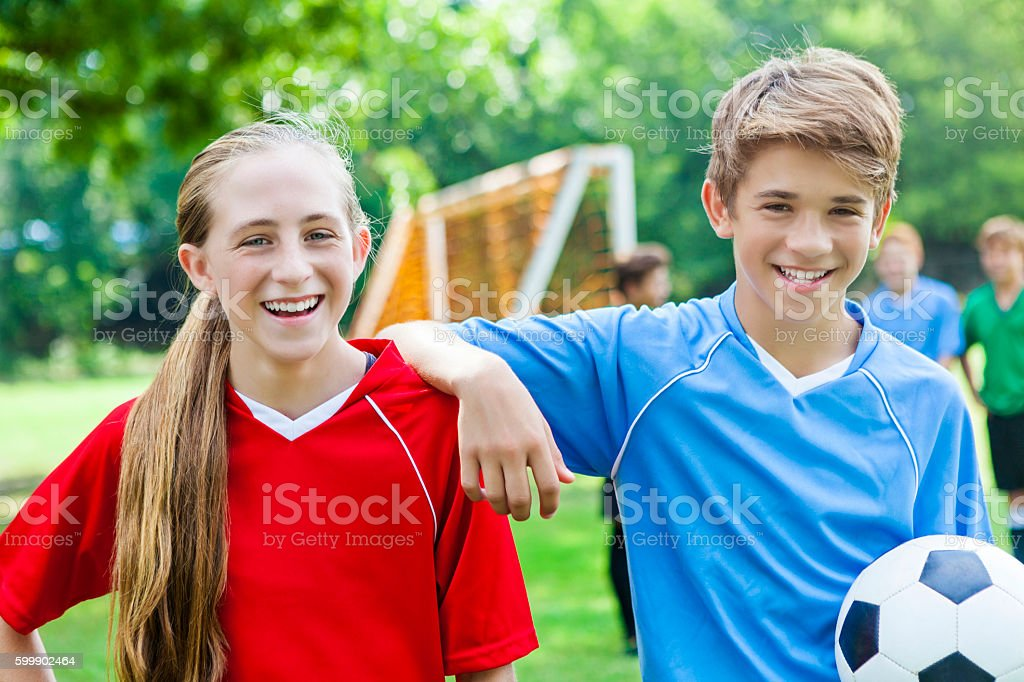 Teenage boy and girl have fun before soccer game stock photo