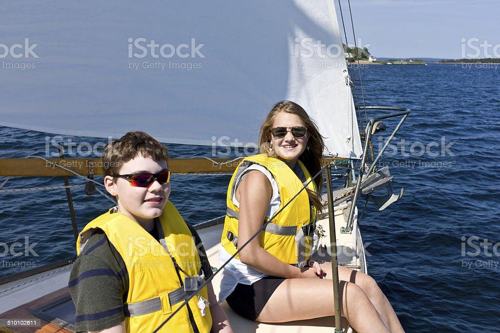 Teenage Boy and Girl Sailing on Mahone Bay, Nova Scotia stock photo