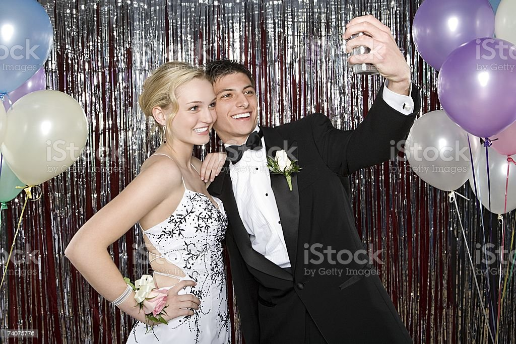 Teenage boy and girl taking a picture at prom stock photo