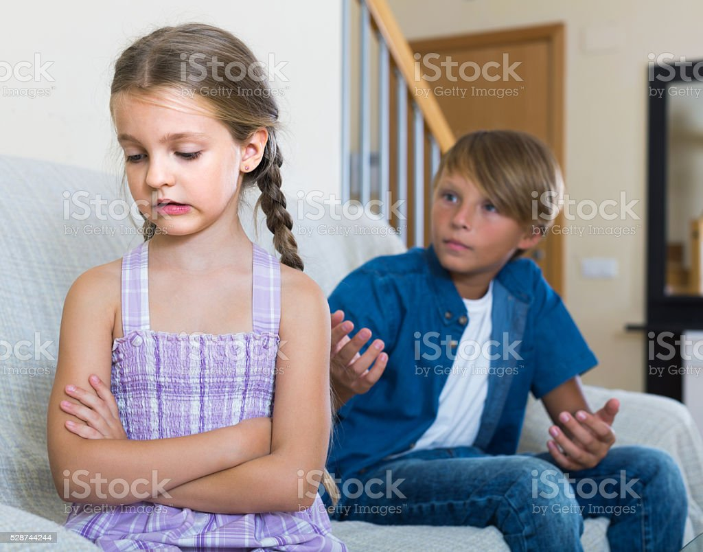 Teenage boy and  little girl quarrelling at home stock photo