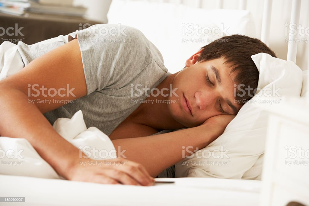 Teenage Boy Asleep In Bed At Home stock photo