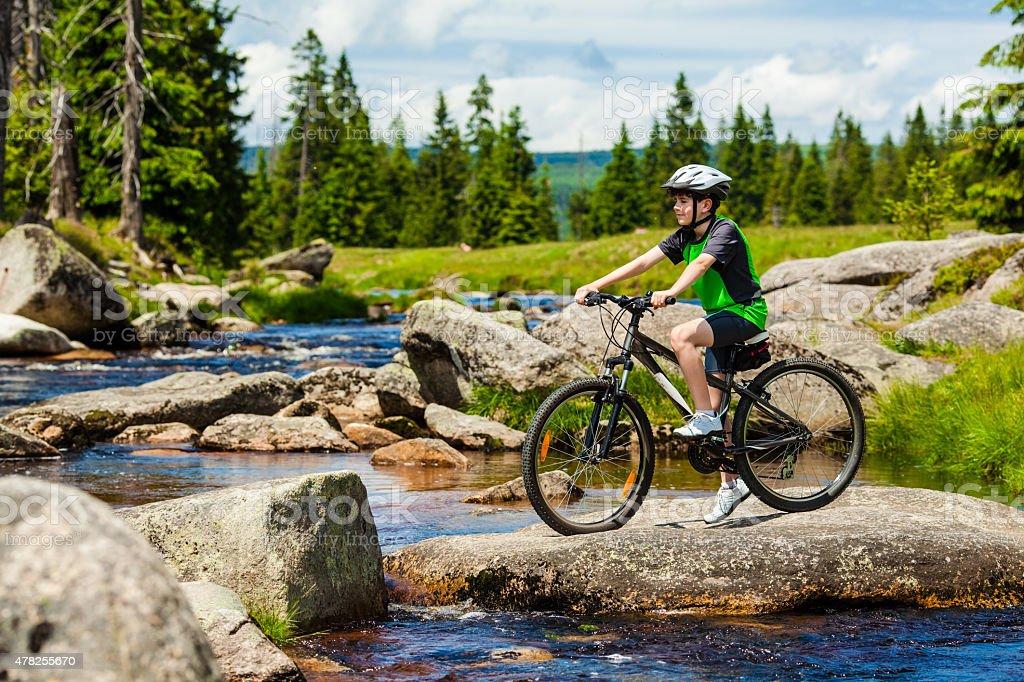 Teenage boy biking on forest trails stock photo