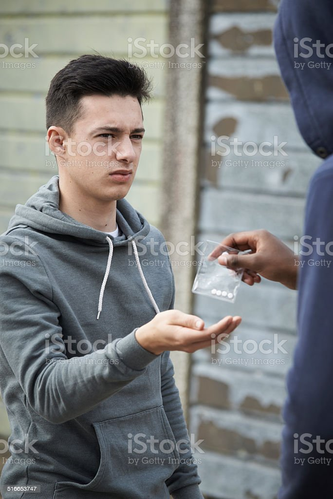 Teenage Boy Buying Drugs On The Street From Dealer stock photo