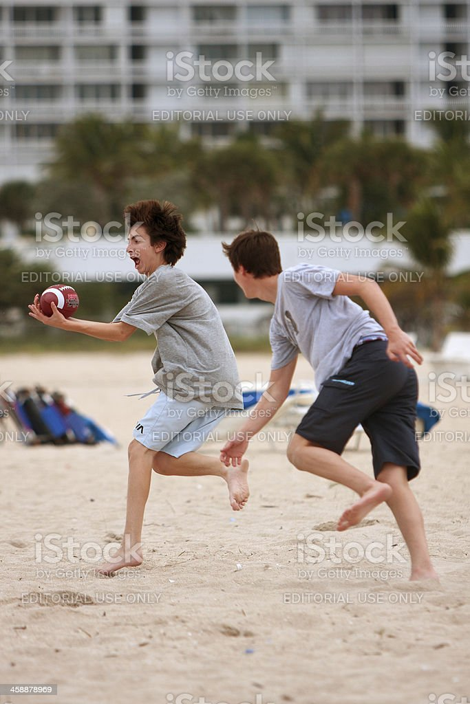 Teenage Boy Catches Ball In Beach Football Game royalty-free stock photo