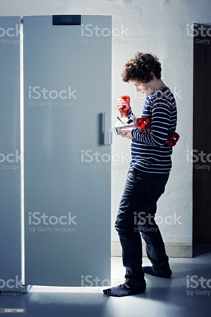 Teenage Boy Caught Getting Late Night Snack From The Fridge stock photo