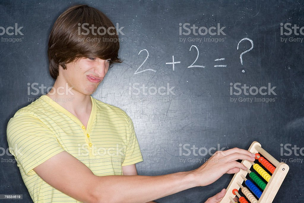 A teenage boy counting on an abacus royalty-free stock photo
